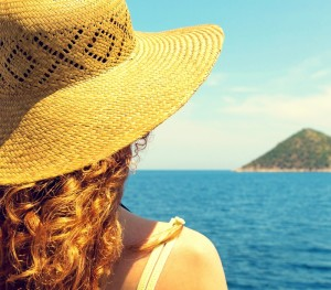 Young curly woman, wearing hat, looking at horizon.